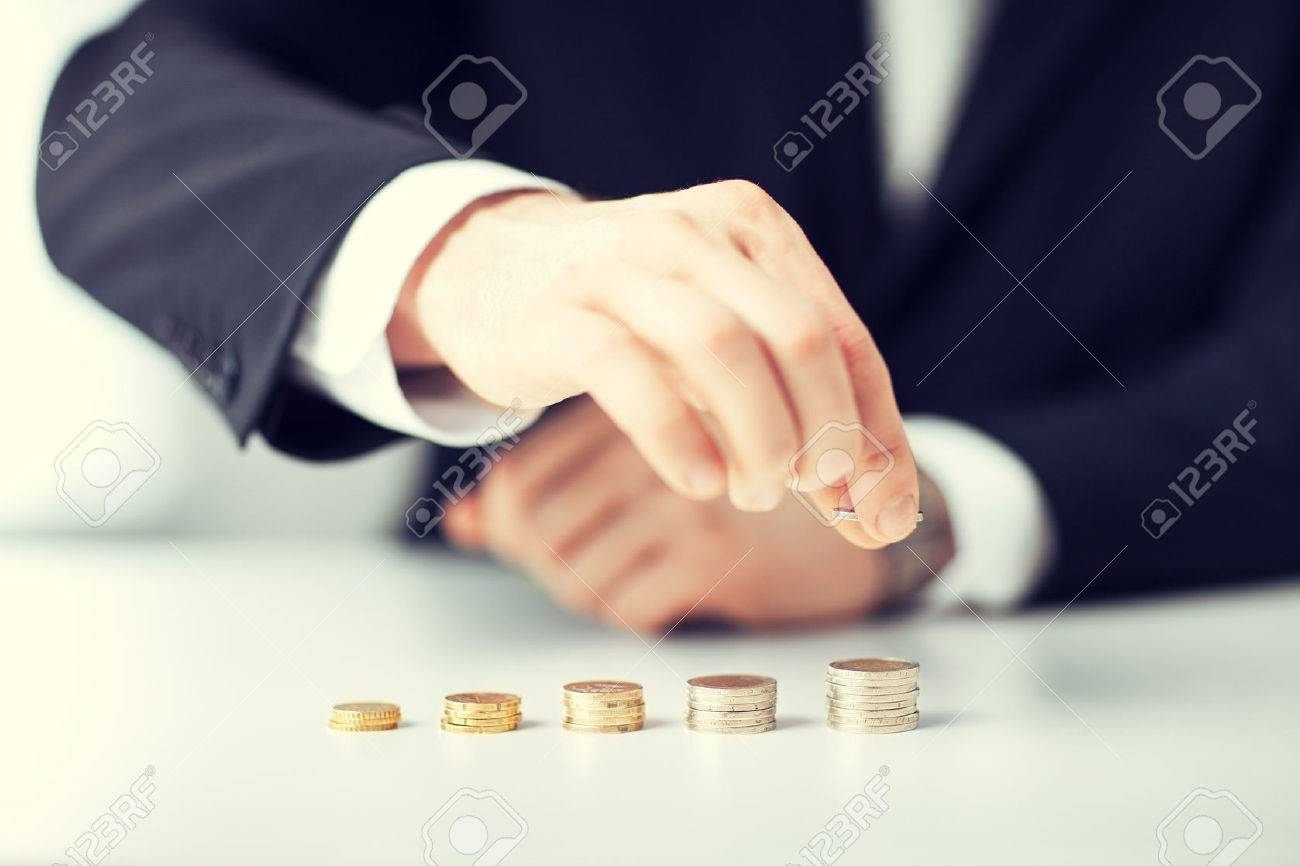 36288905-picture-of-man-putting-stack-of-coins-into-one-row